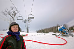 Winter ski vacation. Smiling kid boy stands at the foot of hill with cable lift ski and at this time snow cannon making snowflakes from water Royalty Free Stock Photo