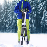 Winter skier teenager sportsman in sportswear with ski standing on snow over snowy forest Royalty Free Stock Images