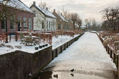 Winter in a small Dutch village. Winter in the historic Dutch village Drimmelen (North Brabant). The canal is almost frozen but the ducks can still swim in the royalty free stock photos