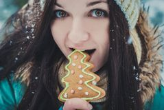 Winter smiling girl eating oatmeal and Gingerbread Cookie outdoor. Lifestyle photo stock images