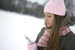 Winter sms. Beautiful young woman reading sms on her cellular phone Stock Photo