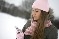 Winter sms. Beautiful young woman reading sms on her cellular phone Royalty Free Stock Photo