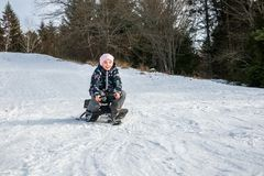 Girl riding a sledge downhill surrounded by trees. stock images