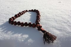 Winter and snow. Christmas beads for prayer. Photo for your design Royalty Free Stock Images