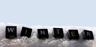 Winter in the snow. Closeup of letter cubes with the word winter in the snow Stock Photos