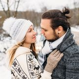 Winter snow couple love story.Beautiful girl in cozy hat and handsome bearded man hugs each other. pullover with. Winter snow couple love story in forest Royalty Free Stock Photography