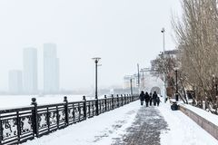 A promenade in Astana. Winter snow-covered avenue in the center of Astana against a background of blurred houses Stock Images