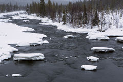 Winter snow-covered banks of the river. Stock Photos