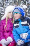 In winter, the snow-covered forest boy with blond girl talk. Royalty Free Stock Image