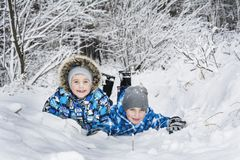 In winter, in a frosty forest, happy boys lie on the snow. Stock Image