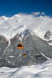 Winter, snow covered mountain with cable cars, sky, clouds Stock Photos