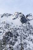 Winter Snow Covered Mountain Summit Peak with Rocky Cliffs on Sunny Day Stock Photos