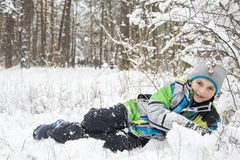 In winter, snow-covered pine forest boy lies near the snowdrift. Stock Images