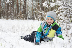 In winter, snow-covered pine forest boy lies near the snowdrift. Royalty Free Stock Photo