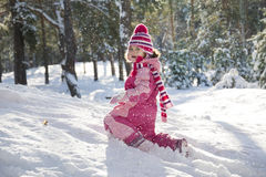 In winter, snow-covered pine forest plays a beautiful little gir Stock Photos