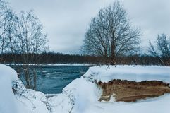 Winter snow covered stormy river landscape. Blue water, waves, and snowy coast with trees. Winter snow covered stormy river landscape. Blue water, waves, and stock images