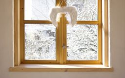 Winter yard seen through the window with angel wings christmas decoration. stock image