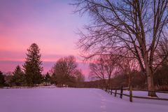 Winter snow at dusk fills the sky with beautiful tones of violet in a fence-lined park. Winter scene stock photos