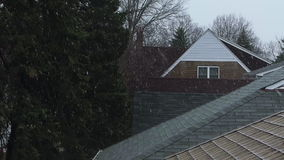 Winter snow falls over the rooftops. A soft snow falls onto the rooftops of houses. The camera is at the height of the rooftops stock video footage