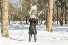 Winter snow fight happy girl throwing snow playing outside. Joyous young woman having fun in nature forest park on snowy day weari royalty free stock photo