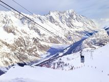 Winter snow mountains rocks in Alps, ski lift and slope Royalty Free Stock Photo