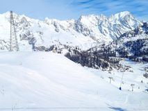 Winter snow mountains rocks in Alps, ski lift and slope Stock Photography