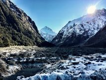 Winter Snow Mountains with Sun Shining. Snow covered mountains illuminated by the sunshine on a clear sky day during the winter in New Zealand. Taken at stock photography