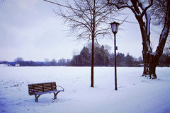 Winter snow in the park, bench and street lamp Royalty Free Stock Image