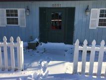Winter snow piled up in front of green door stock photo