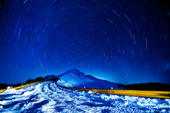 Winter snow road with mountain and star trails Stock Photo