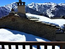 Winter, snow, roof, chimney stack, balcony and mountains. Winter, snow, balcony, roof, chimney stack, mountains, bare trees, sky, cold and nostalgic atmosphere stock photography