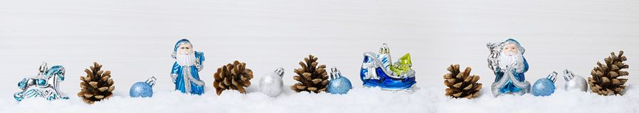 Winter snow scene with blue Christmas decorations on the snow, light wooden background, stock photography