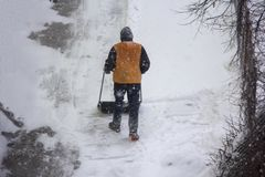 Yard keeper janitor grab snow with a shovel. winter snow sciene. Winter snow sciene janitor grab snow with a shovel Royalty Free Stock Images