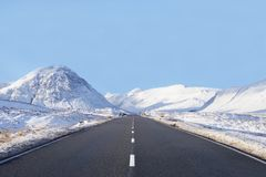 Empty highway road winter snow between mountains blank horizon sky space buchaille etive mor rannoch moor Scottish highlands Royalty Free Stock Images