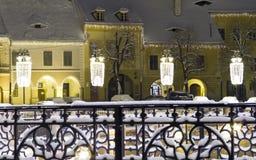 Winter snow town square houses christmas new year. Winter snow christmas lights on street square houses front Sibiu Transylvania Romania winter long exposure Stock Photo
