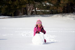 Winter Snowball. Preschooler making a snowball in the snow stock photo