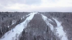 Winter snowboarding and skiing on mountain slope in ski resort top view. Winter skiing on snow slope in ski resort. Aerial view winter extreme on ski lodge stock video footage