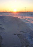 Winter snowbound rural field at the sunset Royalty Free Stock Photo