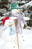 Winter - snowman couple in love in a snowy landscape with a hat Royalty Free Stock Photos