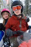 Winter Snowmobile. Brother and Sister riding a snowmobile. Girl is carrying a sledding tube Royalty Free Stock Image