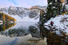 Winter snowshoe hiking by lake at sunrise. Friends hiking by tranquil Blue lake in North Cascades National Park near Winthrop. WA. United States Royalty Free Stock Images