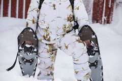 Winter snowshoeing. Man dressed in winter camo clothing, holding snowshoes outside his red cabin in the snow, when Stock Image