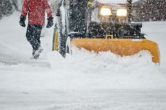 Winter snowstorm. Heavy snowfall winter snowstorm with person walking on city street and snow removal tractor with lights on while snow falls Background image Royalty Free Stock Photo
