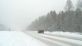 Winter snowstorm on highway. Cars driving through the snow stock footage