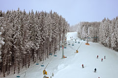 Winter snowy forest and a chairlift for skiers Stock Image