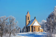 Winter snowy landscape with a church lit by the sun Royalty Free Stock Image