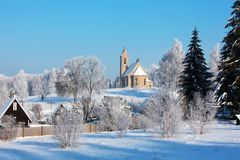 Winter snowy landscape with a church lit by the sun Stock Image