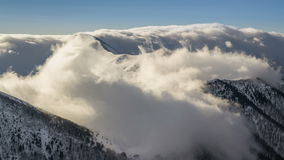 Winter snowy mountains with low clouds flying over ridge in morning light time lapse stock footage