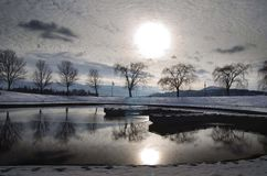Winter Snowy park and pond. Winter scene in a snowy park and pond with sun, clouds, and trees relection Stock Image