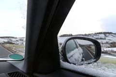 Winter snowy road in the car mirror. Winter snow-covered road in the mirror of the car royalty free stock photography